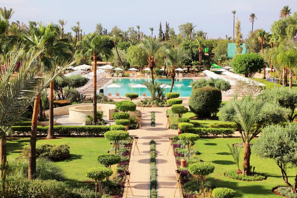 Kappa Club Iberostar à Marrakeck : vue du jardin avec piscine au centre et orné de palmiers.