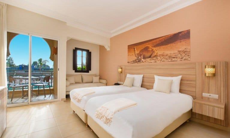 Chambre Iberostar Club Palmeraie Marrakech. Chambre avec lit double et vue sur le jardin + baie vitrée.