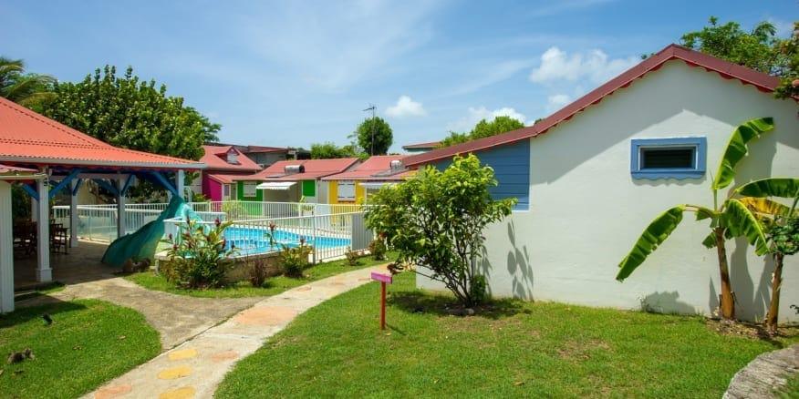 Berceuse créole : gîtes de vacances d'architecture créole et toiture en tôle roule autour d'une piscine.