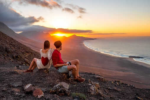 Jeune couple profitant du beau coucher de soleil assis sur la montagne avec vue magnifique sur le littoral de Cofete sur l'île de Fuerteventura aux îles Canaries.