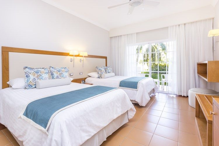 Chambre Deluxe avec deux lit double séparés dans une pièce spacieuse. Chambre avec vue sur le jardin tropical.