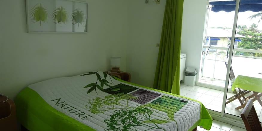 Chambre de la résidence Créoline : lit double avec terrasse et vue sur la piscine extérieure.