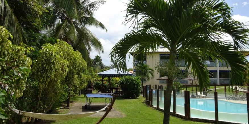 Jardin tropical de la résidence Créoline avec piscine ,carbet et table de ping pong . Résidence cerné de palmiers.