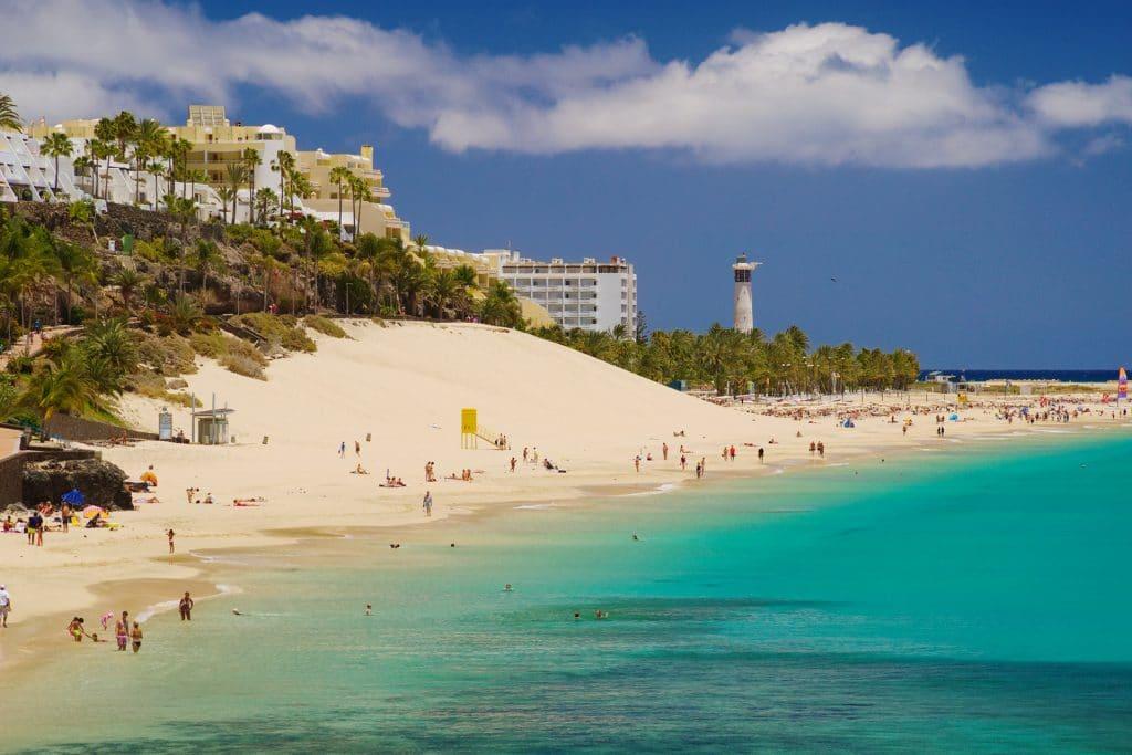 Grande Plage  de Cebada à Fuereteventura, faire de la plongée aux Canaries. Plage avec des nageurs et vacanciers qui bronzent sur le sable.