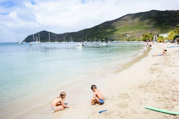 Enfants qui font des châteaux de sables sur la belle plage de Sainte  Luce. Plage avec des catamarans qui mouillent.