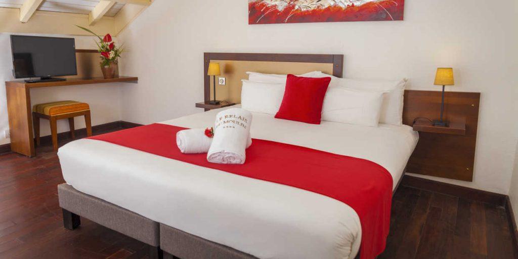 Chambre du Moulin en Guadeloupe: chambre spacieuse avec lit double , parquet.