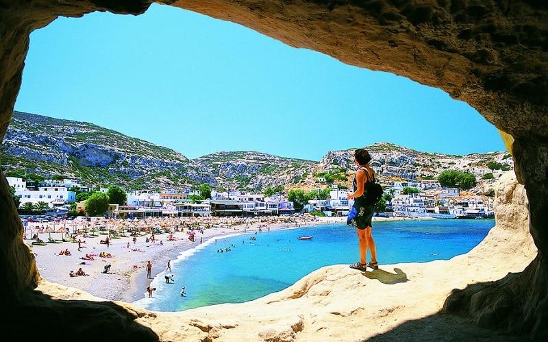 Plage de Crète perçu par une grotte avec une vue magnifique . Des vacanciers sur la plage bronzent et nagent
