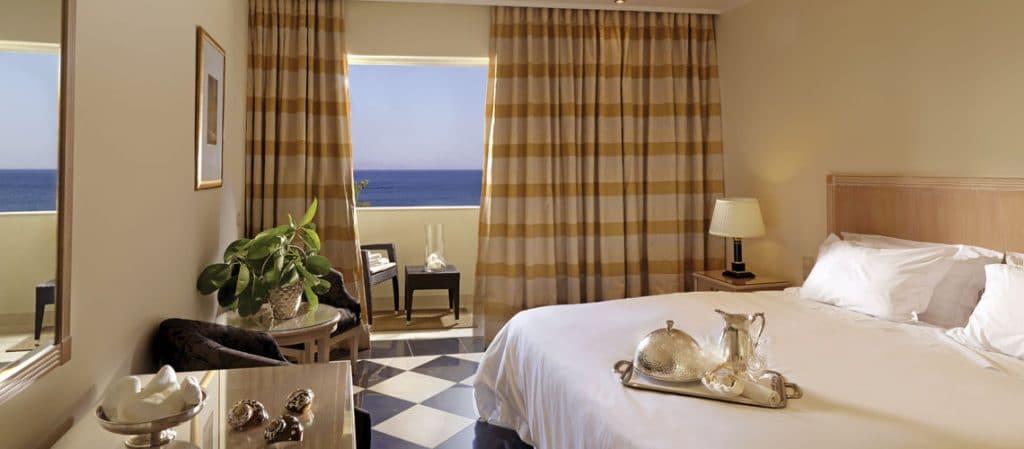 Chambre de l'hôtel pour un voyage tout compris en Crète. Chambre spacieuse de l'hôtel 5 étoiles avec lit double + terrasse, plateau petit déjeuner posé sur le lit . Vue magnifique sur la méditerranée.