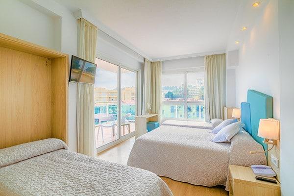 Chambre avec 3 lits double pour accueillir 6 adultes ou 2 adultes avec des enfants. Chambre spacieuse avec télévision + grande terrasse avec baie vitrée, balcon élégant  pour un formidable voyage en Espagne.