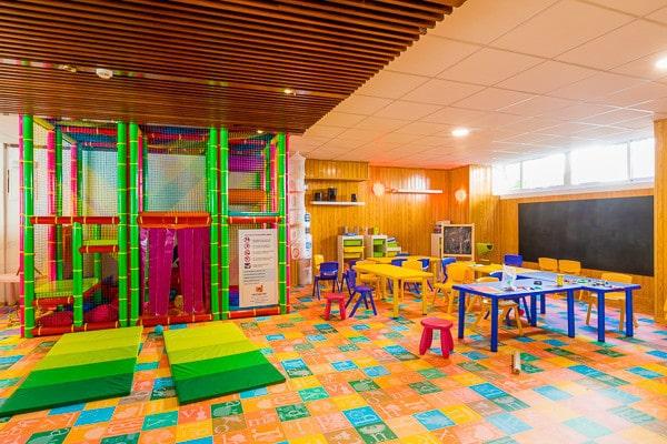 Parc de loisir pour enfant  avec des jeux  et des tables + chaises . Lieu de loisir avec feutres et crayon de couleur pour que les enfants puissent jouer.