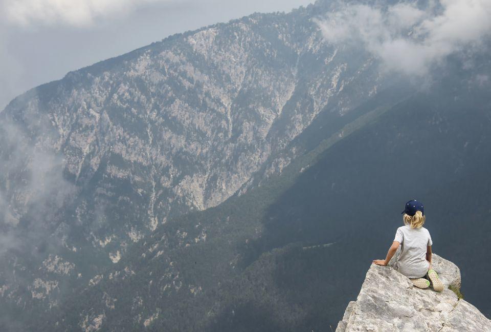 Enfant au sommet du mont Olympe en Grèce . Il admire le paysage et les montagnes.