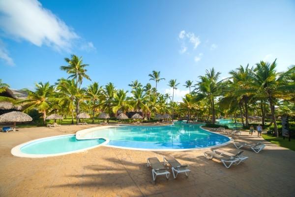 Piscine extérieure de l'hotem Maxi club Punta Cana en République Dominicaine. Belle piscine avec 2 bassin s entourés de cocotiers, palmiers , carbets , transats faisnat face à la mer