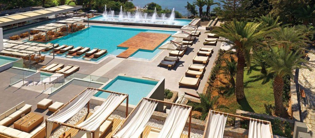Vue aérienne de la piscine du Club de vacances avec des transats , chaises allongées et des jets d'eaux. Un lieu idéal pour bronzer au soleil pendant son séjour en Grèce.