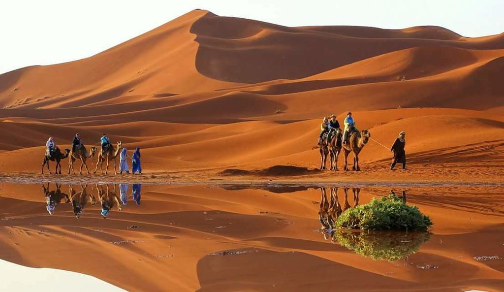Circuit touristique dans le desert du Sahara au Maroc : effet optique mirage sur le sable .