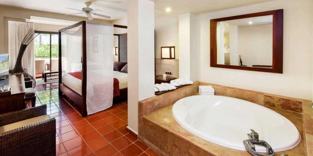 Chambre de luxe avec salle d'eau et grande terrasse avec vue sur le jardin tropical .