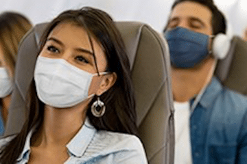 voyageur dans un avion avec le masque : destination pays sans isolement